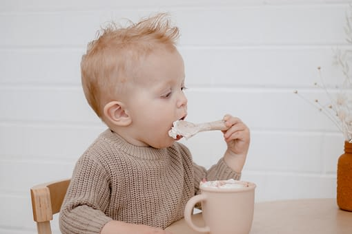 Ginger toddler eating a babyccino with a spoon. He is wearing a beige jumper.