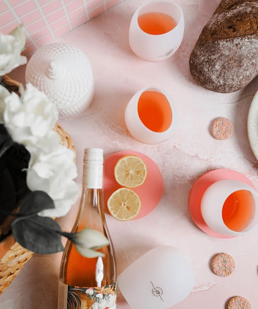 Overhead shot of silicone wine glasses and wine bottle, sliced lemons and biscuits are also in the flatlay image