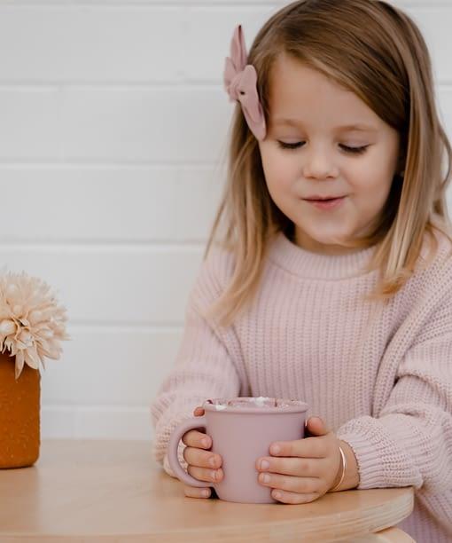 Girl drinking babychino cup.